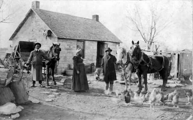 People standing in front of a small home in Dunlap, Kansas holding horses and with chickens in the foreground