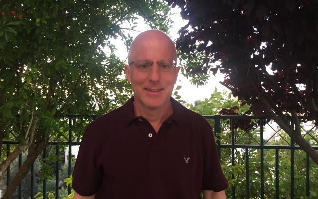 Man with glasses in maroon shirt with trees in background