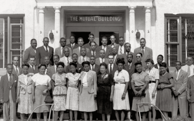 About three dozen well-dressed African American men and women posing in front of a business in the 1900s