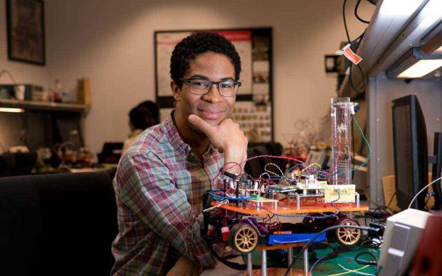 Student with a robotic vehicle he invented