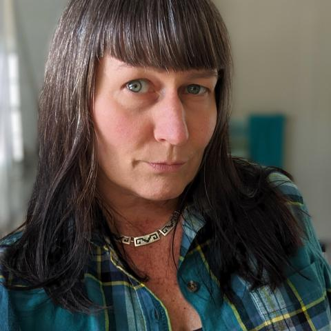 woman wearing a blue-green plaid shirt and long hair with bangs